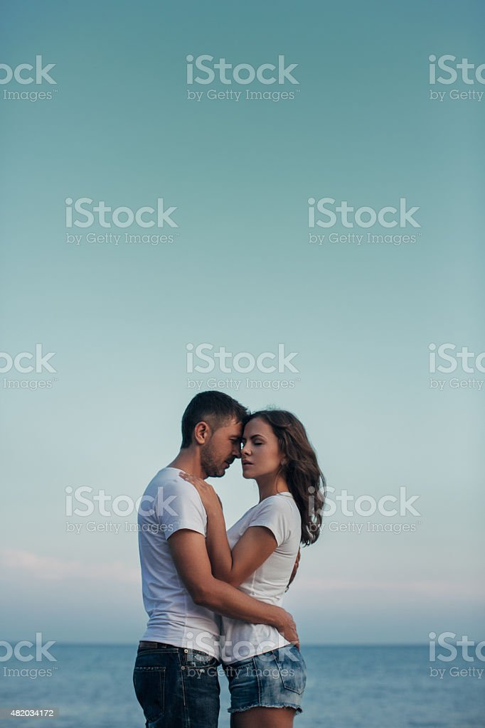 Two people embracing each other on the background of sea coast
