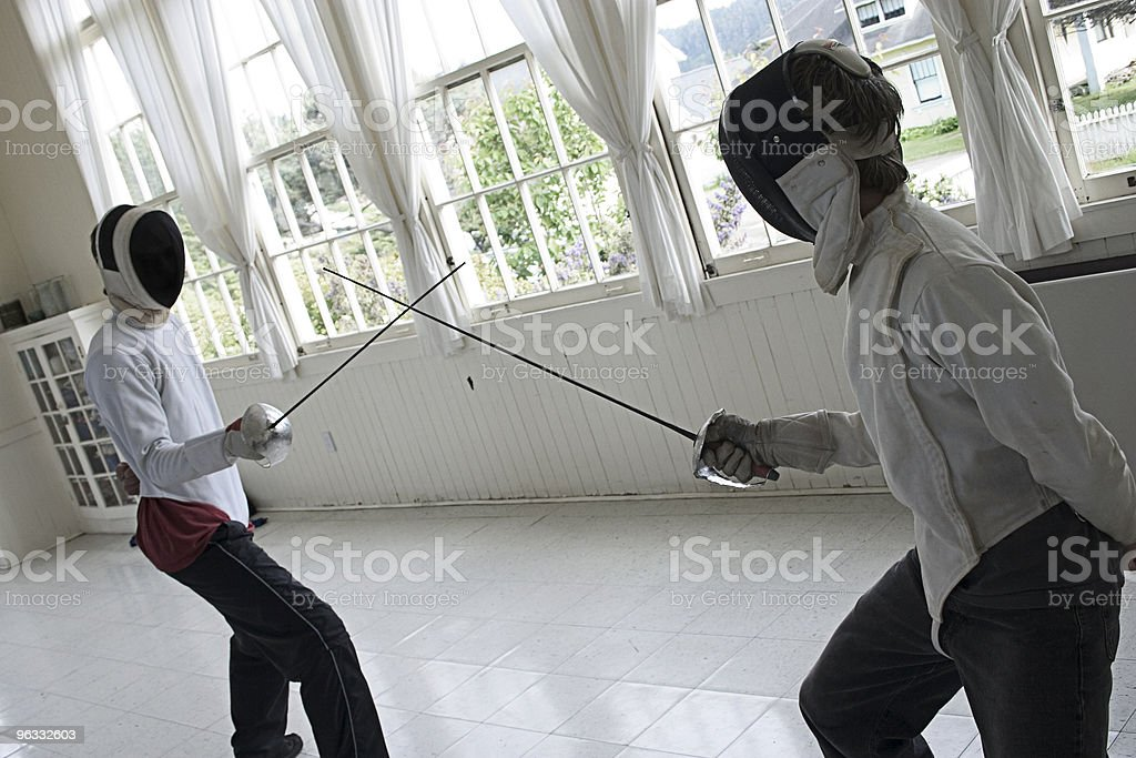 Two people fencing in a white room royalty-free stock photo