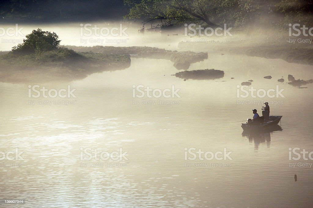 Two people fishing in a boat in misty water stock photo