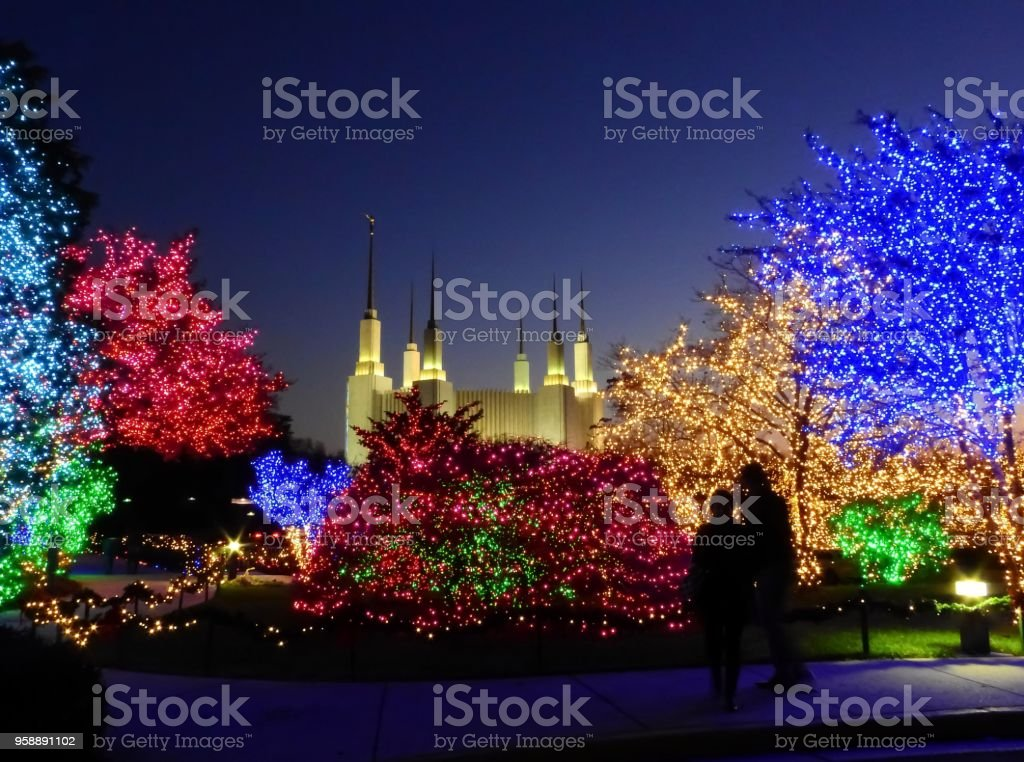 Silhouette of two people standing and gazing at the holiday lights at...