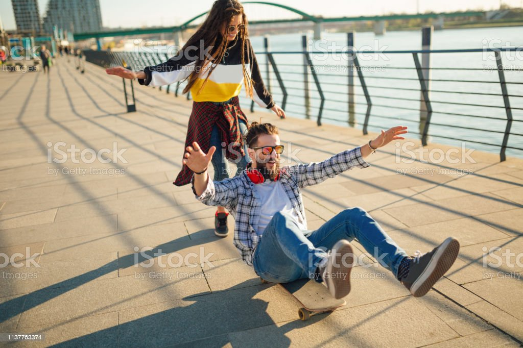 Hipsters, man and a woman, goofing around and having fun on...