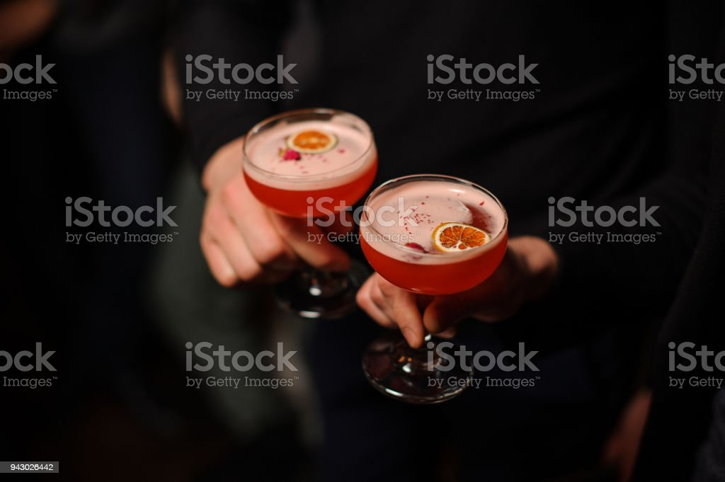 Two people dressed in black holding cocktail glasses filled with...