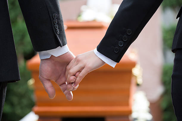 Two people holding hands at a funeral Religion, death and dolor - couple at funeral holding hands consoling each other in view of the loss mourner stock pictures, royalty-free photos & images