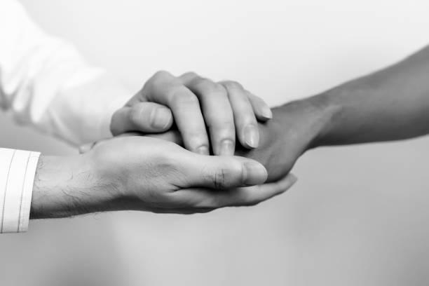 Zwei Menschen Hand in Hand für Komfort. Arzt tröstet Angehörige von Patienten im Krankenhaus-Konzept. schwarz und weiß. – Foto