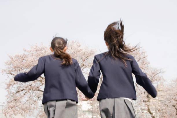 繋いで、実行女子中学生二人 - 中学校 ストックフォトと画像