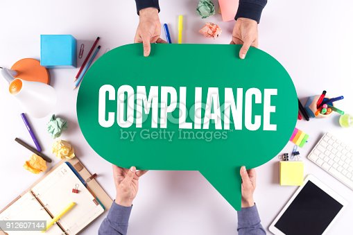 istock Two people holding speech bubble with COMPLIANCE concept 912607144