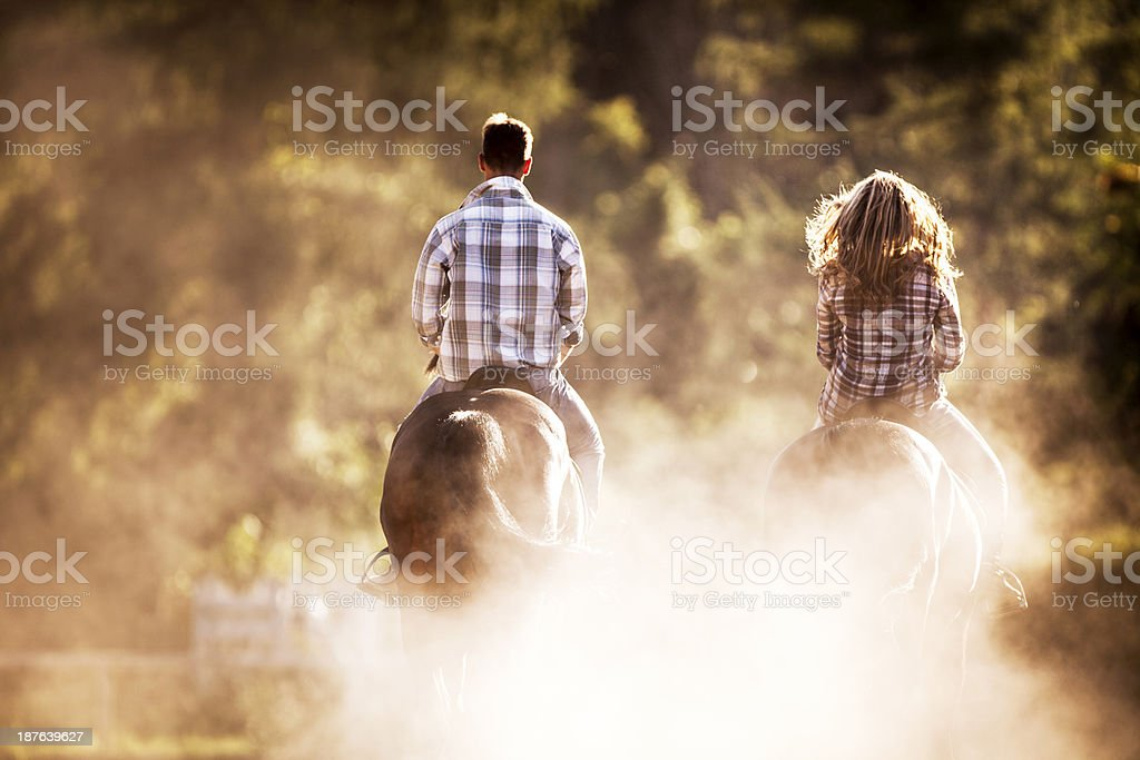 Two people horseback riding. stock photo
