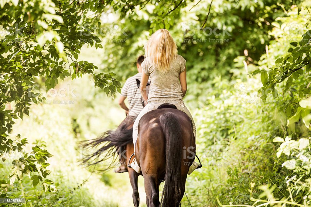 Rear view of two unrecognizable people horseback riding in nature.