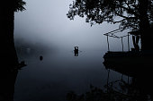 Landscape of two people in a boat in a lake covered with fog, centre framed reflection silhouette, taken at Naukuchiyatal, Uttrakhand, India