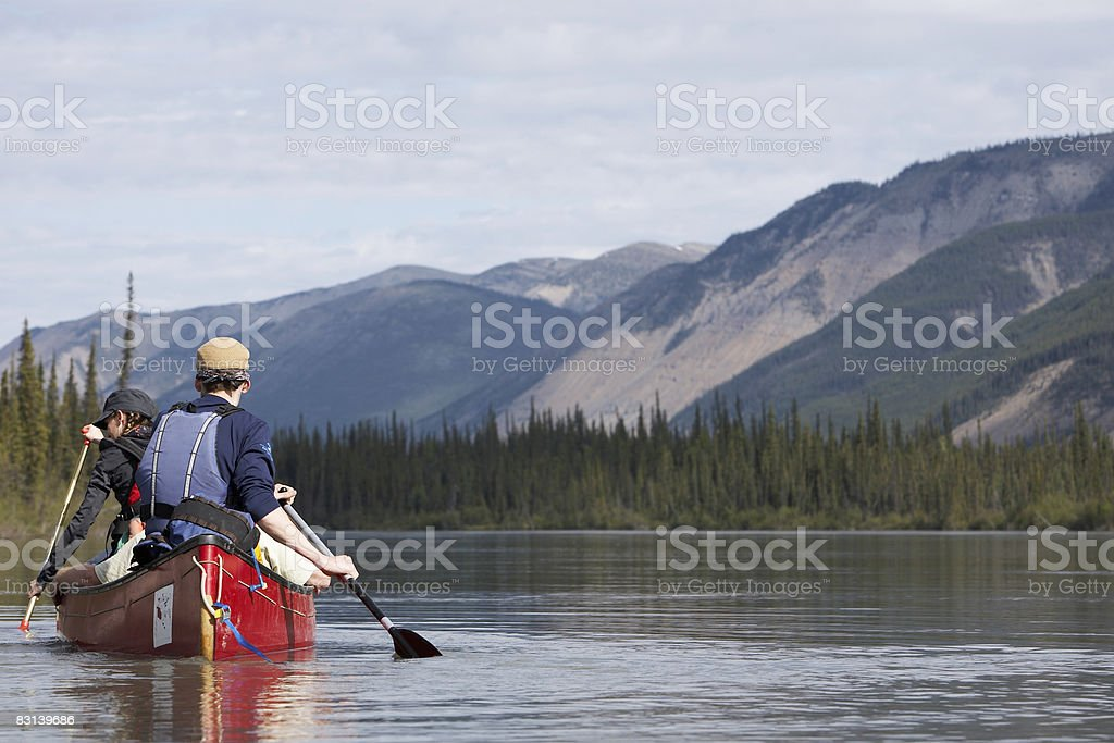 two people in canoe on calm water zbiór zdjęć royalty-free