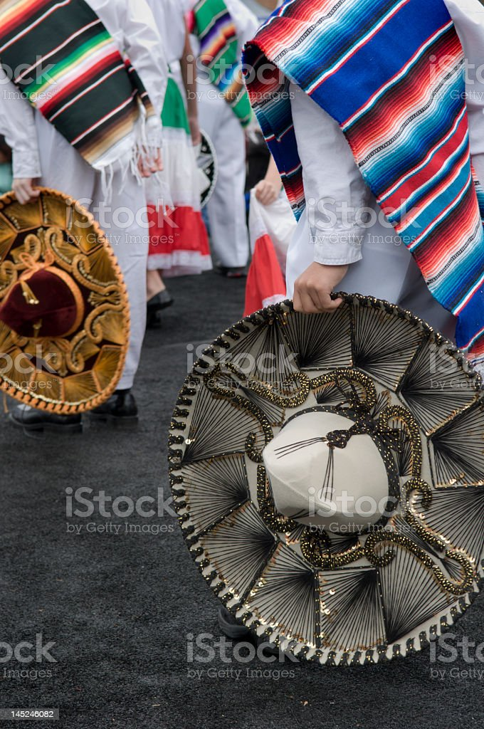 Two people in costumes holding colorful sombreros royalty-free stock photo