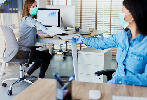 istock Two people in office passing documents with keeping a distance 1220761973