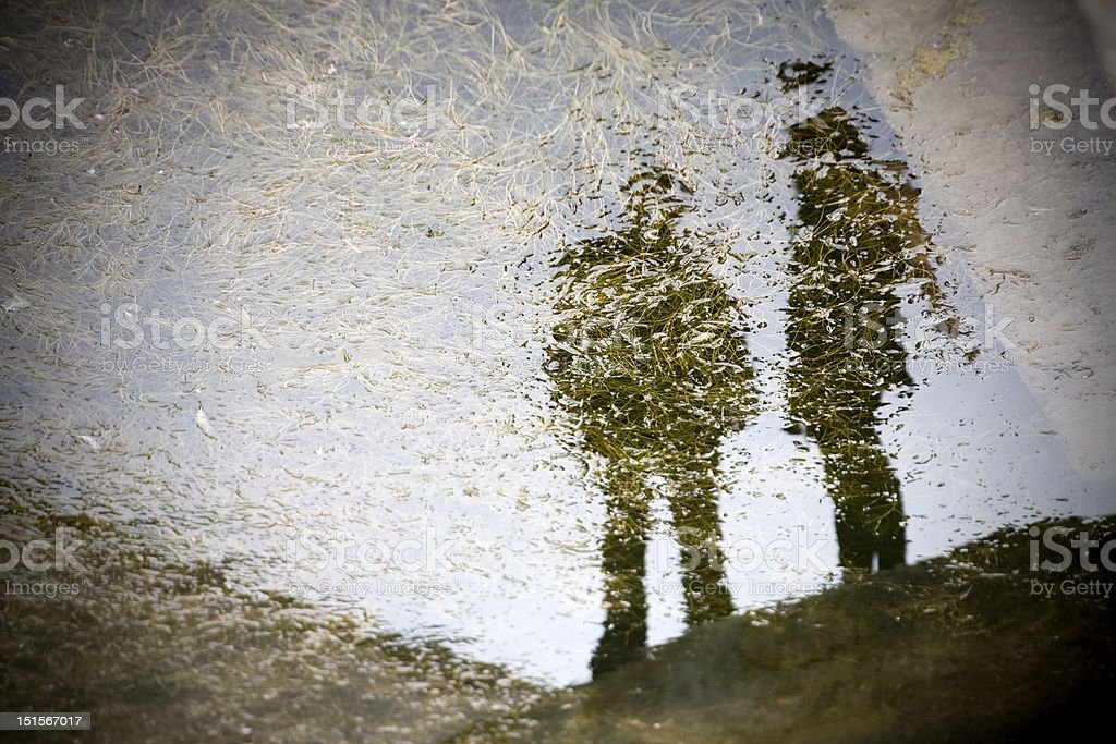 Two People in Reflection Two people reflecting in the murky water in San Francisco, Ca. Abstract Stock Photo