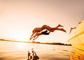 istock Two people jumping in water against the sunlight. 170036801