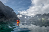 Two people kayaking in Milford Sound, New Zealand