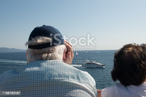 istock Two people looking out to sea with super yacht passing bye 1168183187