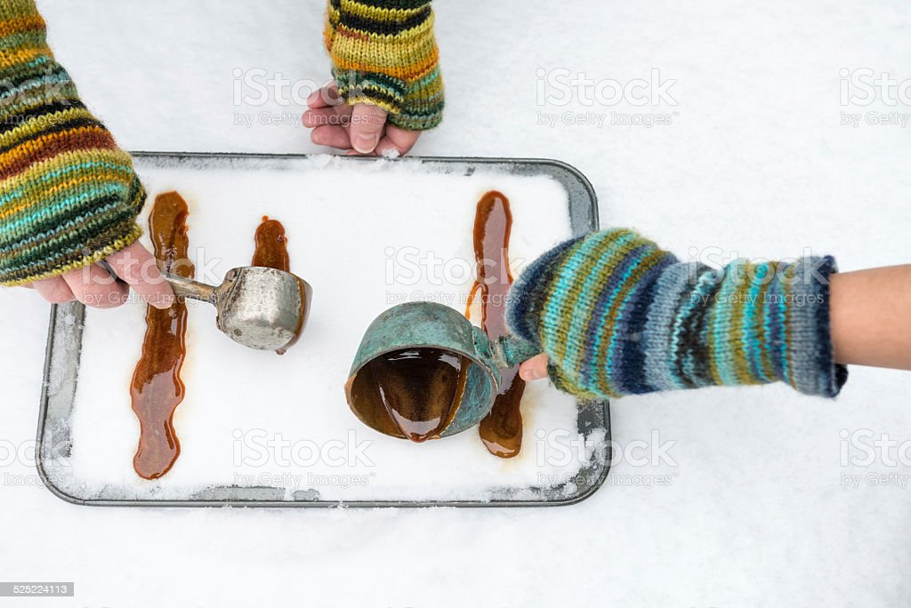 Two People Making Maple Syrup Taffy in Snow stock photo