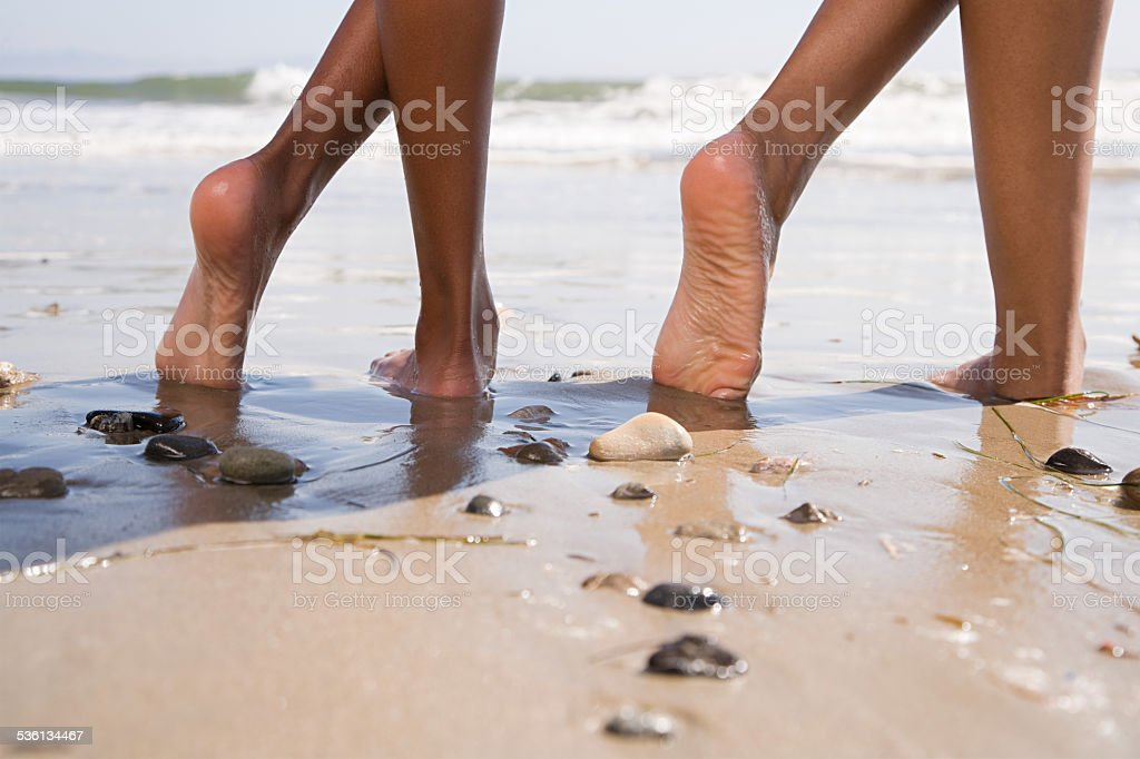 Two people on beach with crossed legs stock photo