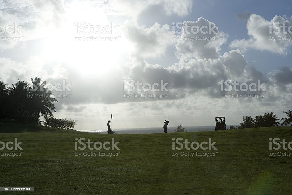 Due persone sul campo da golf, giocando a golf all'alba foto stock royalty-free