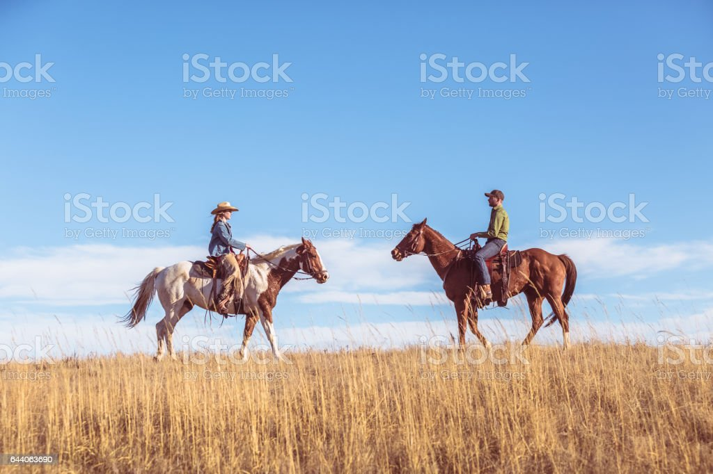 Two People On Horseback Riding Toward Each Other stock photo