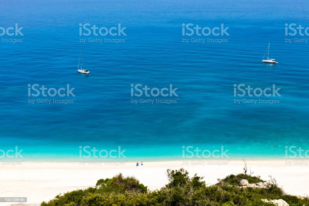 Two people on the beach and two yachts in the sea stock photo