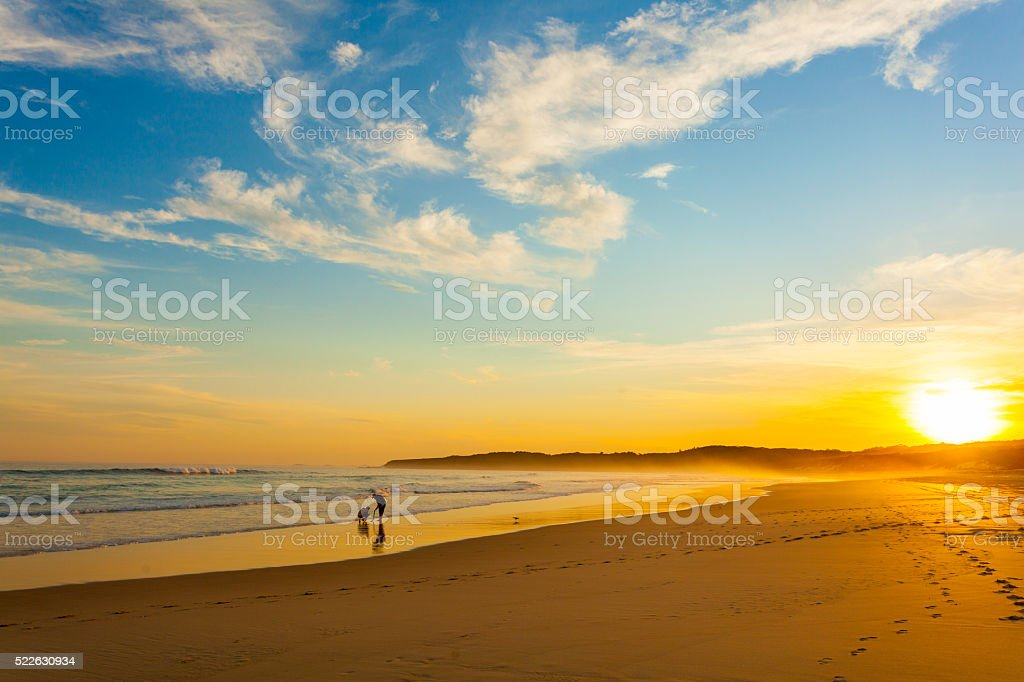 Two people on the beach at sunset, Australia stock photo