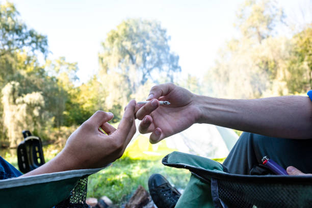 Two people passing a cannabis joint between them outside at a campsite. stock photo