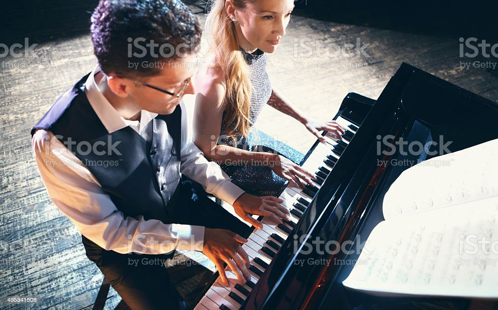 Two people playing piano. stock photo
