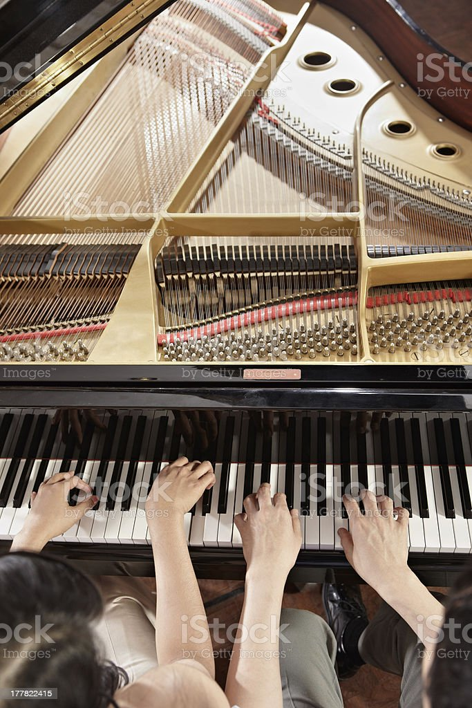 Two people playing piano seen from above with cover lifted stock photo