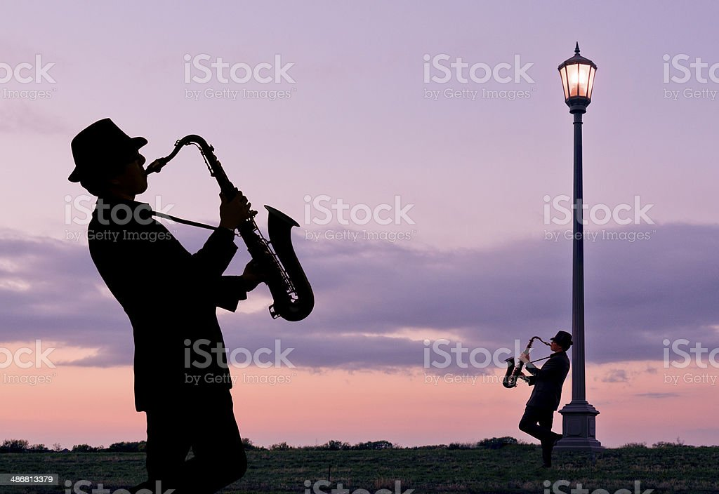 Two people playing saxophones beside Street Lamp stock photo