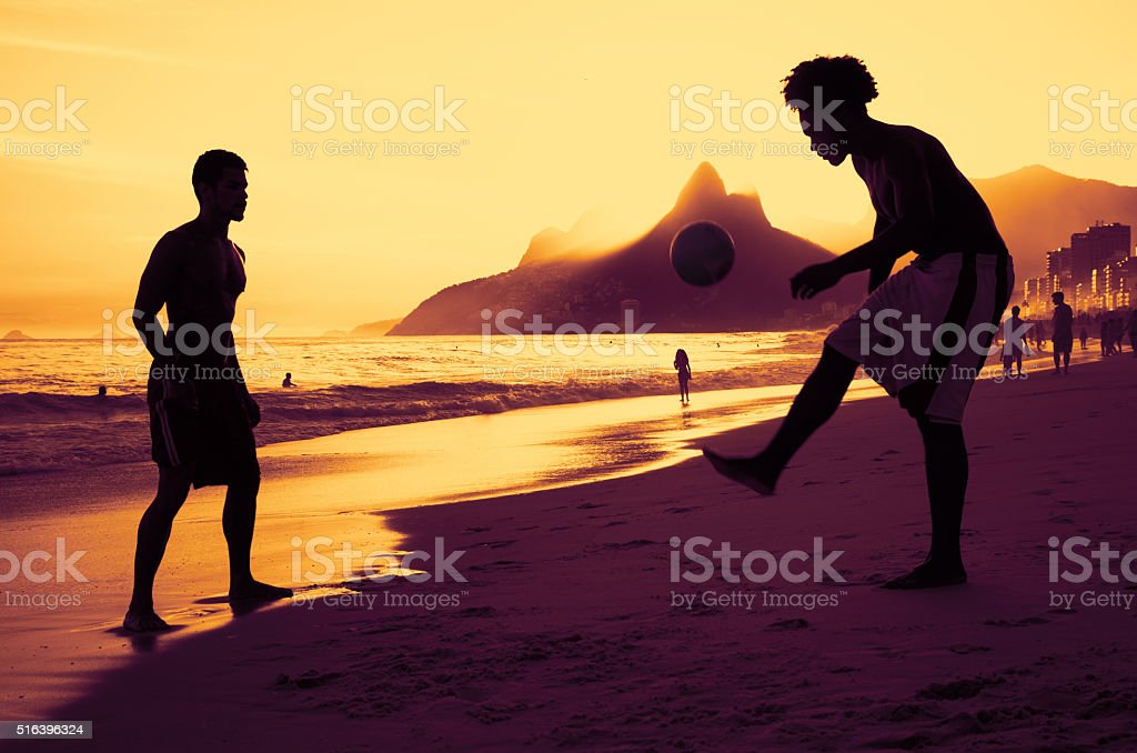 Two people playing soccer at beach at Rio at sunset stock photo
