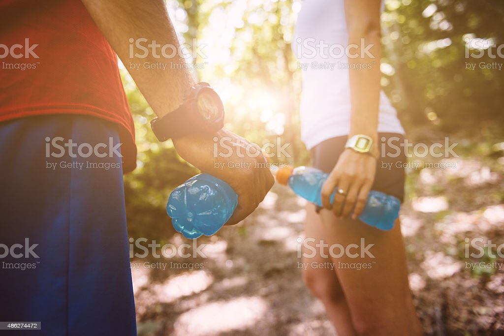 Close up of two person posing on a trail in the forest wearing a pair...
