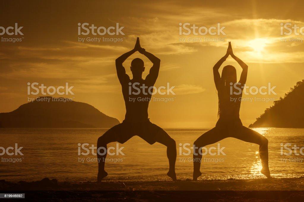 Two people practicing yoga