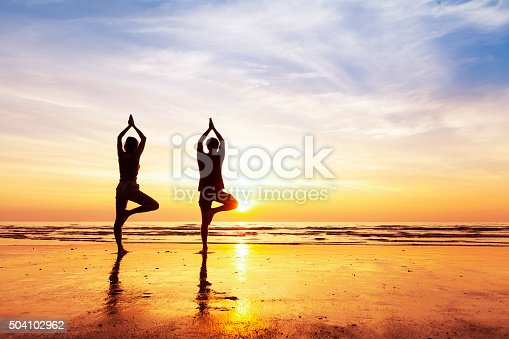 istock Two people practicing yoga tree position on the beach, sunset 504102962