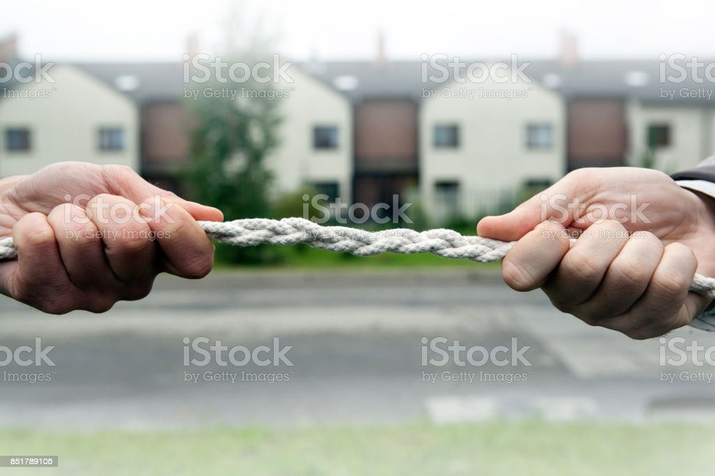 two people pull the rope against each other stock photo