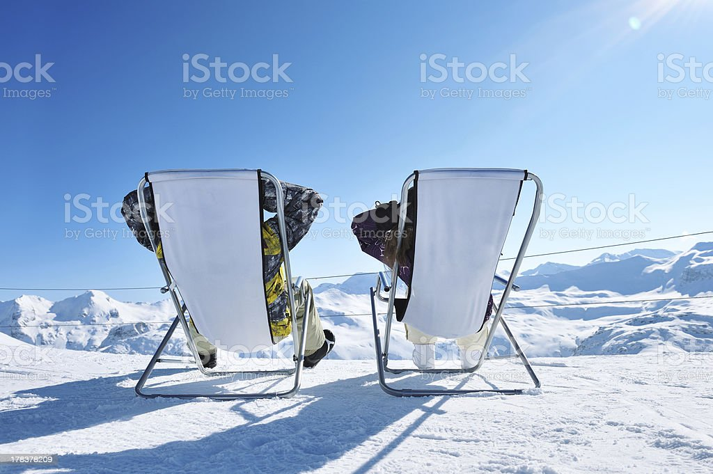 Two people reclining in chairs on a snowy mountain stock photo
