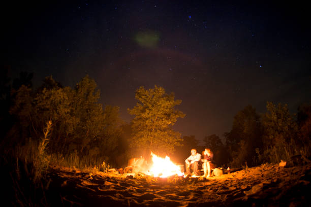Two People relaxing around a camp fire stock photo