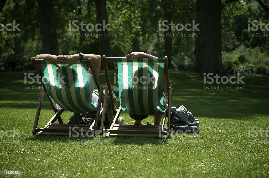 Two People Relaxing in Striped Deck Chairs London Park Two people kick back in striped lawn chairs in lush green summer park British Culture Stock Photo