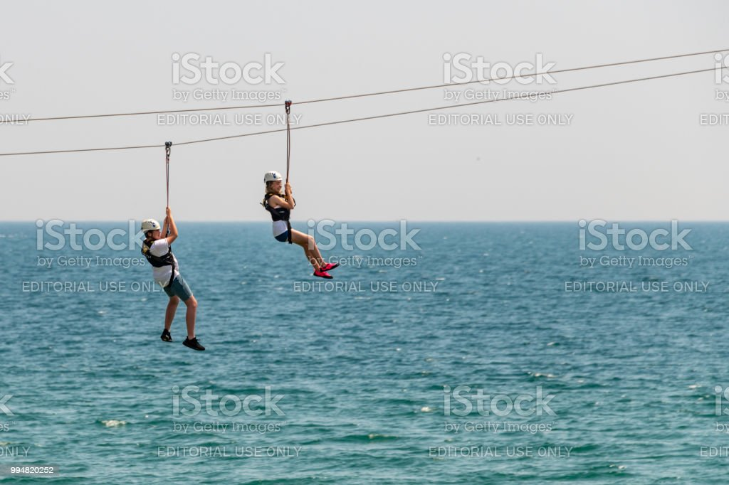 Two people ride the zip wire over the sea in Bournemouth stock photo