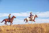 A man and woman on horseback, racing up a grassy hill in Montana on a sunny day with golden grass and blue sky. Cowgirl is in the lead.