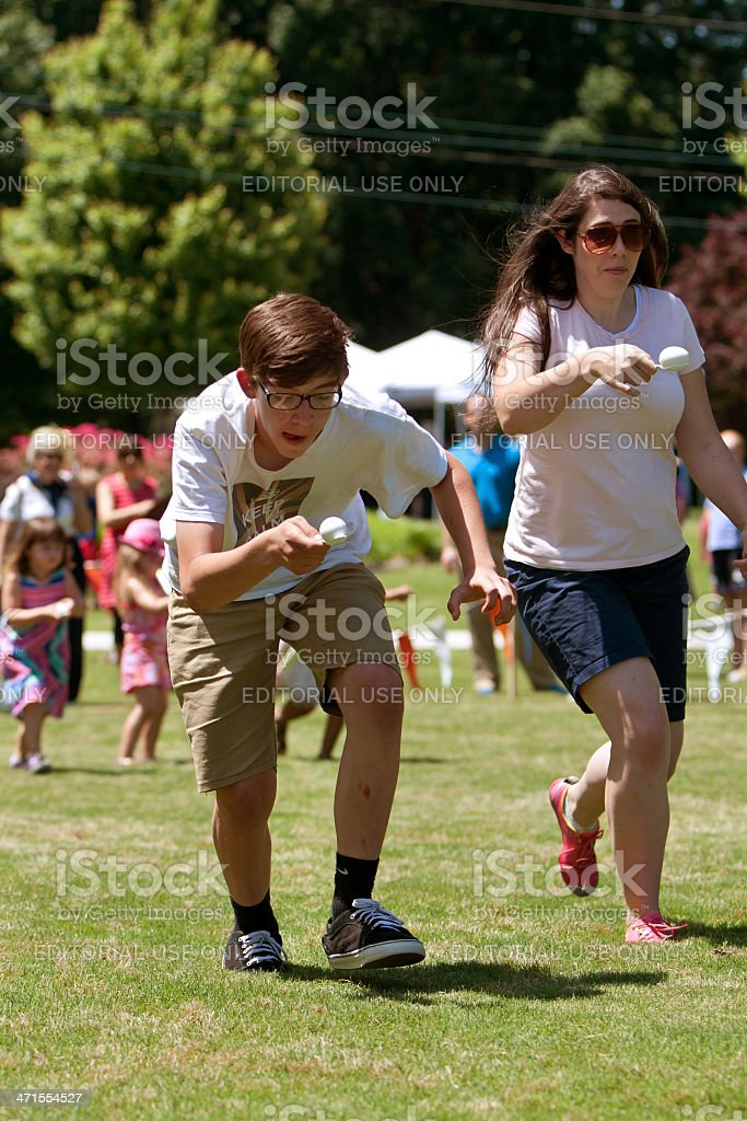 Two People Run In Egg and Spoon Race At Festival stock photo