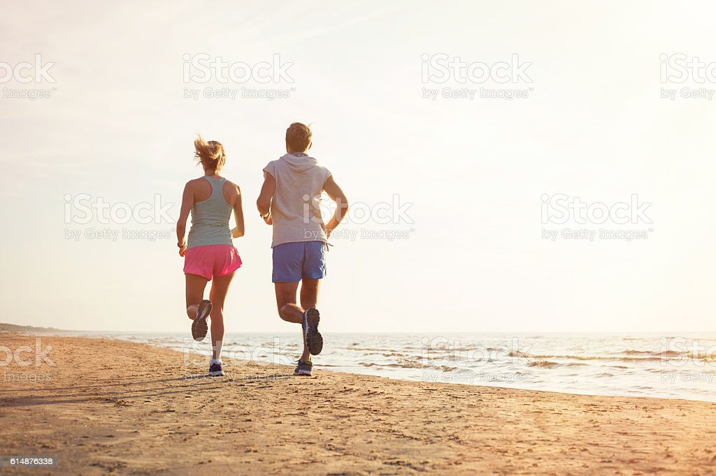 Two people running on the beach stock photo