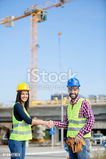 617878058 istock photo Two people shaking hands at construction site 618947924