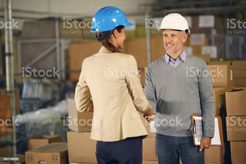 Image of two people shaking hands in warehouse