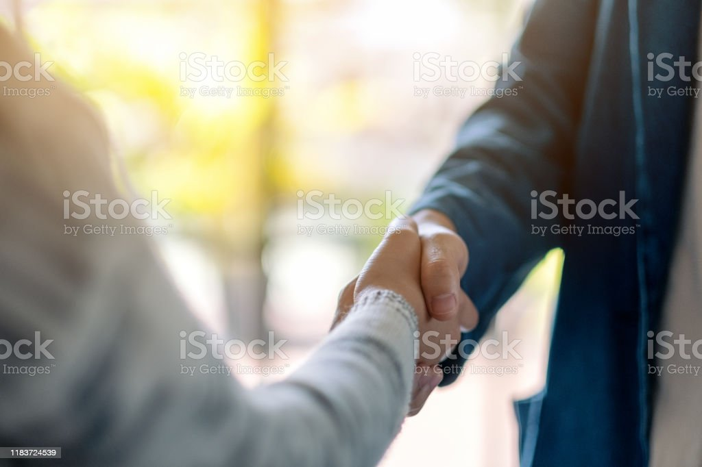 two people shaking hands Closeup image of two people shaking hands Adult Stock Photo