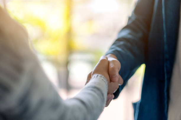 two people shaking hands - handshake stock pictures, royalty-free photos & images