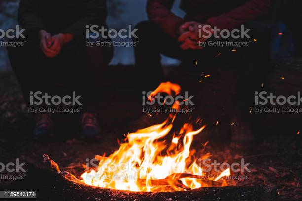 Photo of Two people sit by the bright bonfire at dusk.