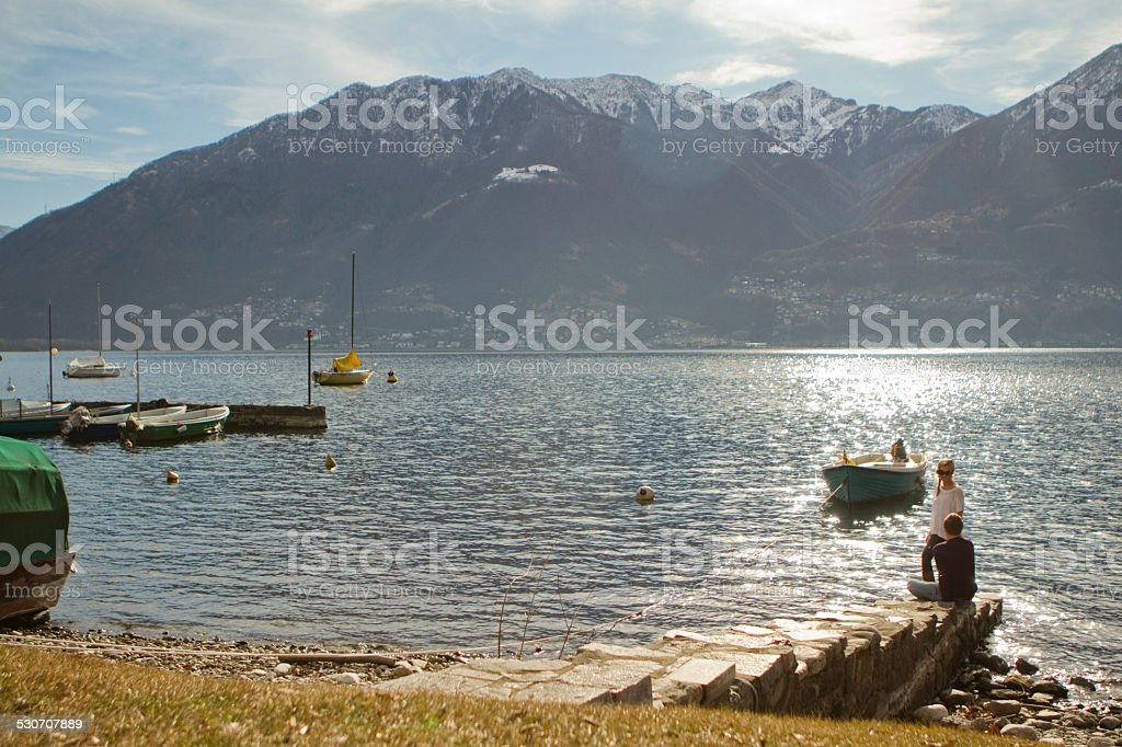 Two people sitting near the lake stock photo