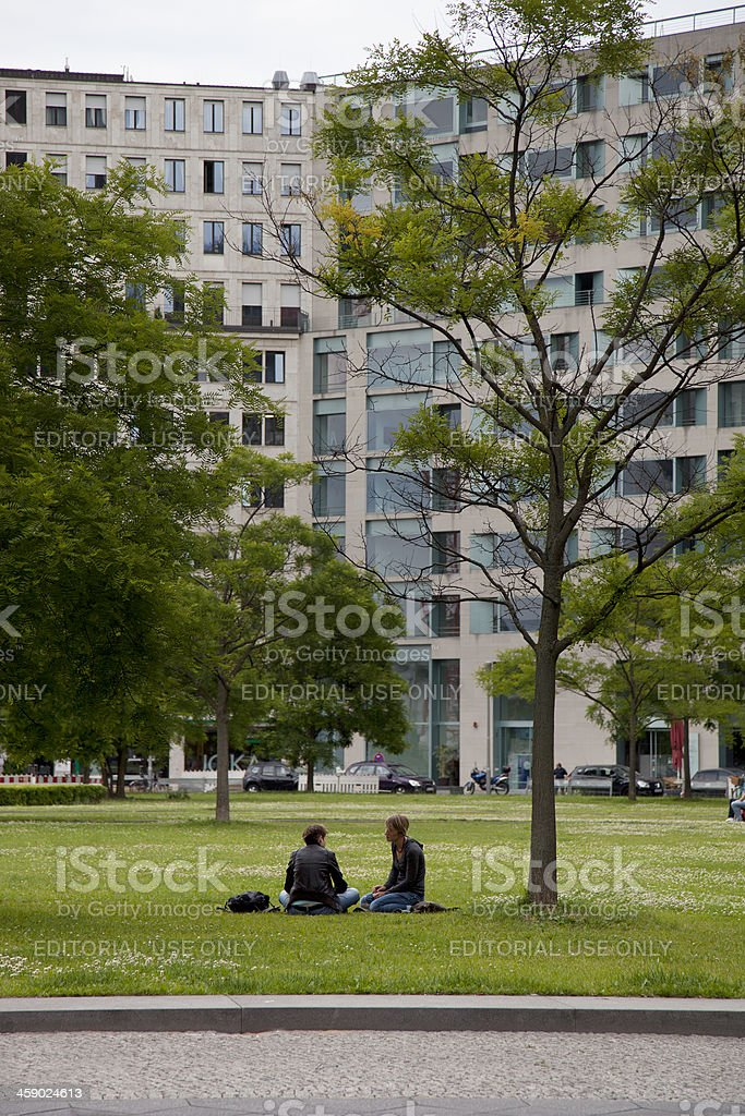 Two people sitting on grass at Potsdamer Platz royalty-free stock photo
