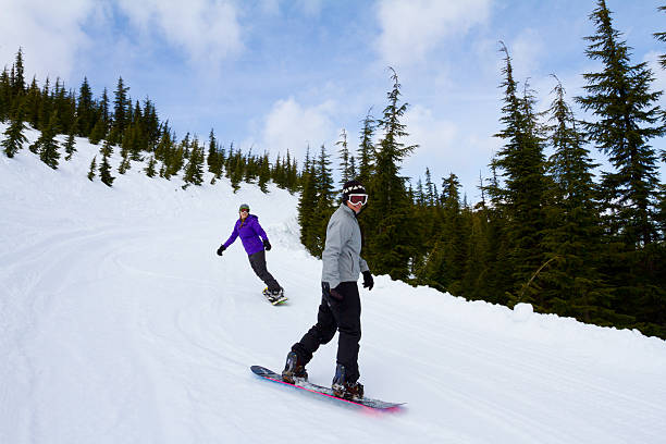 Two People Snowboarding Together stock photo